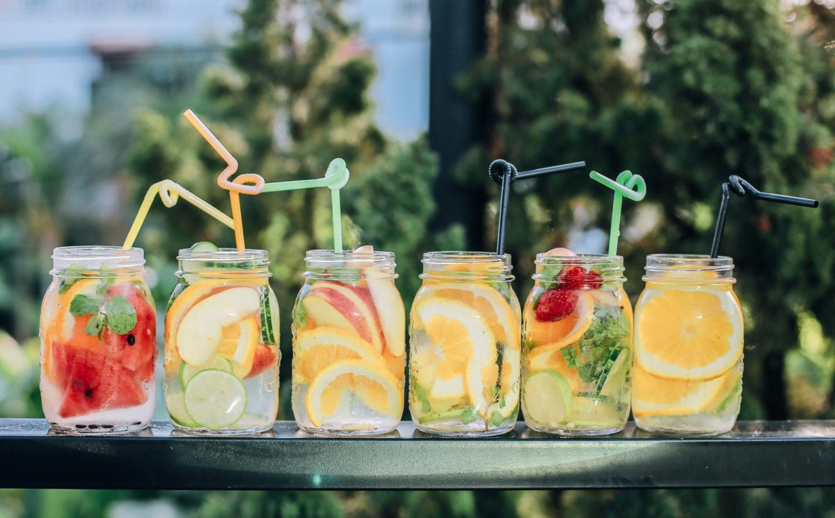 Fruit and water in jars with straws