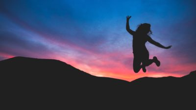 Woman exercising, jumping with sunset in background